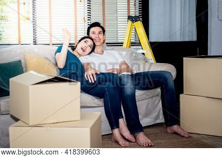 Asian Young Couple, Husband And Attractive Wife Are Happiness And Sitting On The Sofa After Being Ti
