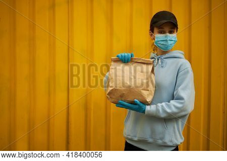 Girl Courier In A Medical Mask And Medical Gloves On Yellow Background. Delivery Service In Quaranti