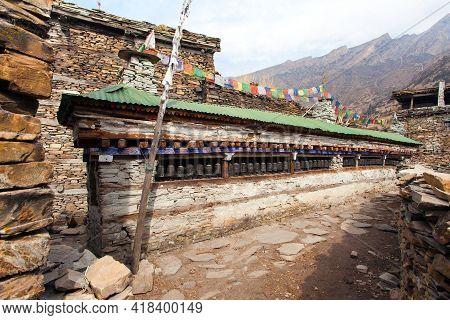 Buddhist Prayer Many Wall With Prayer Wheels In Nepalese Village, Round Annapurna Circuit Trekking T