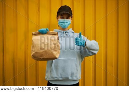 Girl Courier In A Medical Mask And Medical Gloves. Delivery Service In Quarantine. Caucasian Cute Wo