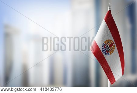 A Small Flag Of French Polynesia On The Background Of A Blurred Background