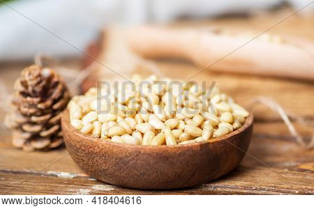 A Wooden Round Bowl With Pine Nuts Is On The Table, Next To A Pine Cone. The Distant Shot Is Blurred