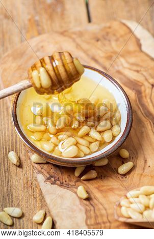 A Plate With Honey And Pine Nuts, A Honey Spoon With Transparent Honey Dripping From It. Light Woode