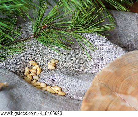 A Gray Linen Cloth With Pine Nuts On It, A Green Pine Branch With Needles, Next To It Is A Wooden Sa