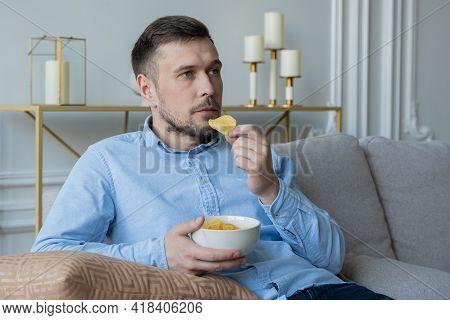 Man Sits On The Couch And Eats Potato Chips