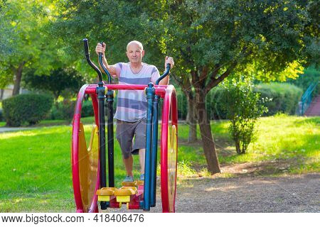 Happy Older Man Working Out On The Sports Public Equipment In The Outdoor Gym.a Sportive Active Elde