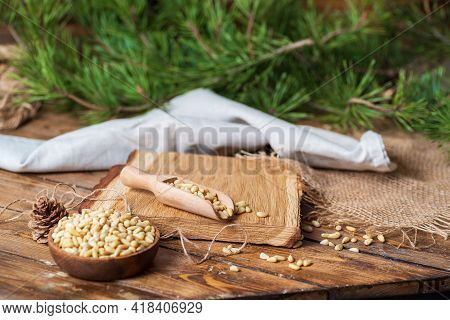 A Bowl And Scoop With Peeled Pine Nuts Stand On A Board On A Wooden Table. Nearby Lies A Gray Rough