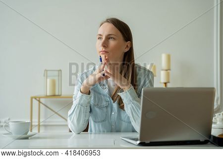 Young Woman Working At The Laptop And Looks Thoughtfully Into The Distance While Sitting At Her Work