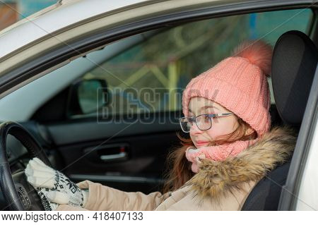 Teenage Girl In A Jacket In The Car. A Girl In A Pink Hat And A Beige Jacket In The Car. Car, Girl