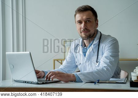 Doctor Using Laptop In Medical Office. Man Is Working With Documents And Laptop In His Medical Offic