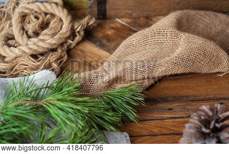 On A Wooden Table Lie Coarse Gray Fabrics, A Linen Rope, On Top Of A Pine Branch With Long Needles,