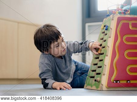 Indoor Portrait Preschool Boy Playing In Kid Club, Child Having Fun Playing Colorful Toys In Kid Pla