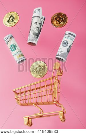 Dollar Bills And Itkon Coins Flew Out Of The Golden Basket On A Pink Background. Concept