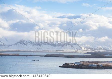 Reykjavik Bay, Iceland. Coastal Landscape With Snowy Mountains Under Cloudy Sky