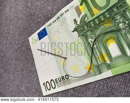 Black Thread With A Needle Are On The 100 Euro Banknote. The Background Is Fabric Grey. The Banknote