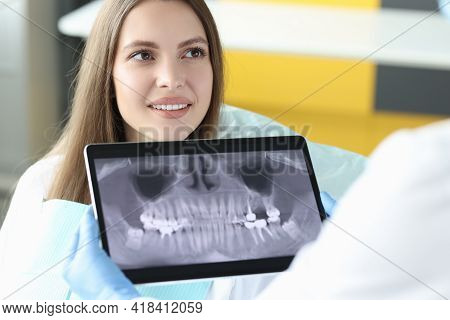 Portrait Of Smiling Woman At Dentist Appointment Holding Tablet With An X-ray Image Of Jaw