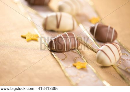 Extreme close up of gourmet date chocolates with confetti. Beautiful photo of exotic date chocolates.