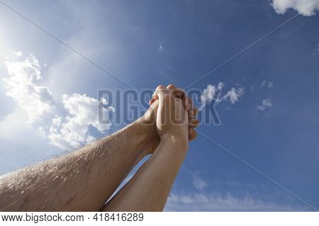 Male And Female Hands Together Against Blue Sky
