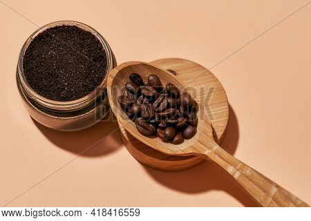 Facial Scrub In Open Can And Wooden Spoon Filled With Coffee On Light Orange Background, Top View. B