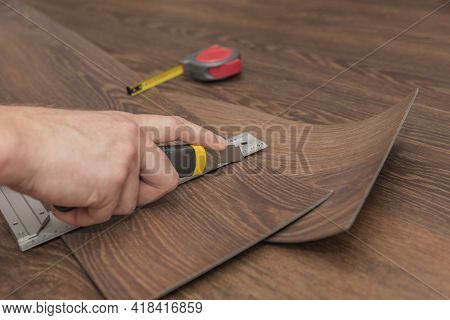 The Process Of Laying Vinyl Flooring In Public Places, Cutting Brown Vinyl Floors. Resistant Floors
