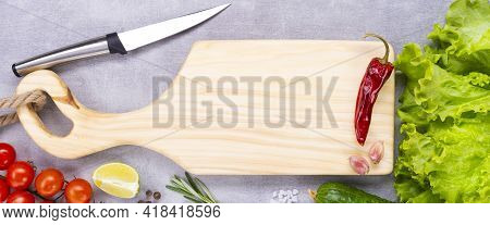 Cutting Board With A Knife On The Table. Handmade Chopping Board. Fresh Vegetables, Spices And A Cut