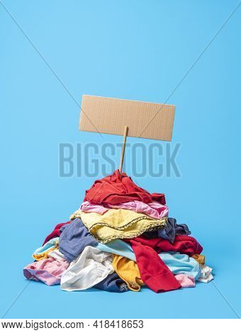 Pile Of Used Clothes With A Cardboard Sign Prepared For A Text. Recycling Used Clothes Concept. Colo