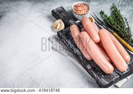 Chicken And Turkey Meat Raw Sausages On A Wooden Board With Thyme. White Background. Top View. Copy