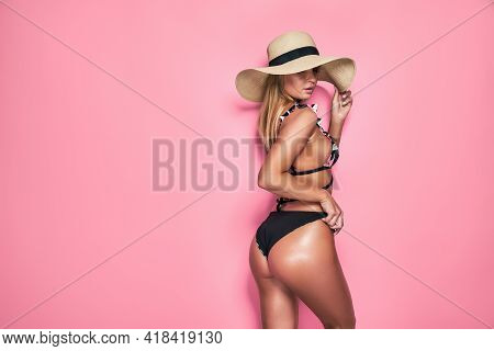 A Gorgeous Trendy Fit Woman In Swimwear And Hat While She Enjoying Rest With Sunlight Isolated Over