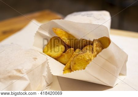 Fried Potato Wedges Wrapped On The Table Close Up