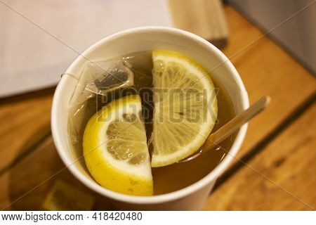 Tea With Lemon Slices In A Plastic Glass Close Up