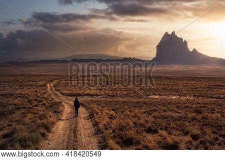 Woman Walking On A Dirt Road In The Dry Desert With A Mountain Peak In The Background. Dramatic Suns