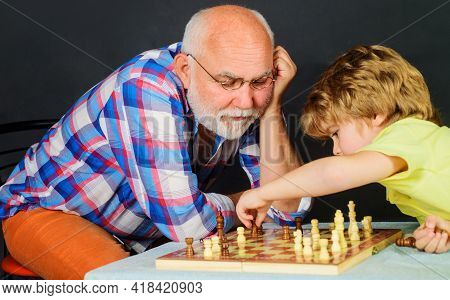 Chess Competition. Grandpa And Grandson Playing Chess Spending Free Time Together. Brain Development