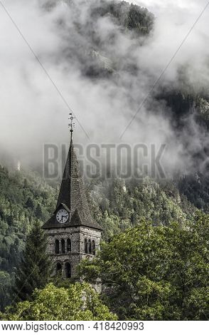 Bell Tower Of A Church With A Big Clock In A Mountain Village In The Pyrenees With Clouds Behind It
