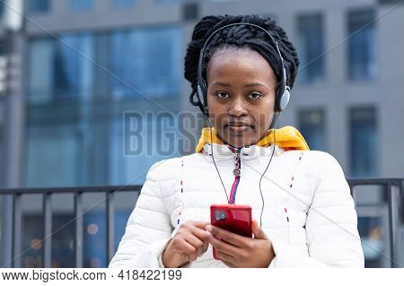 Beautiful Sad Brooding Style Black Girl Listen Music With Headphones On Mobile Phone Outdoor. Happy