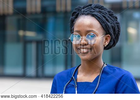 Smart Black Girl Medical Student In Glasses, Happy Young African American Woman Doctor In Blue Unifo