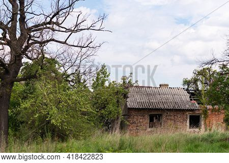 Old Village House Near Krakow. Abandoned Brick House After Fire. Old Slate And Charred Beams.