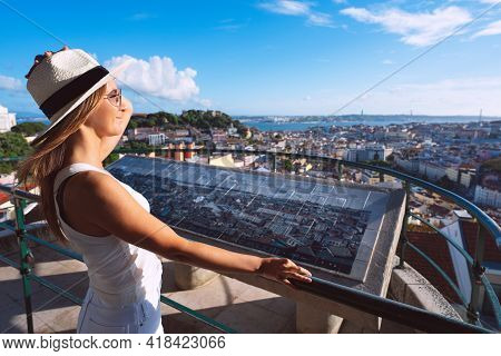 Young Woman Tourist In White Hat Walking In Lisbon City And Looking At Beautiful View. Travel And Va