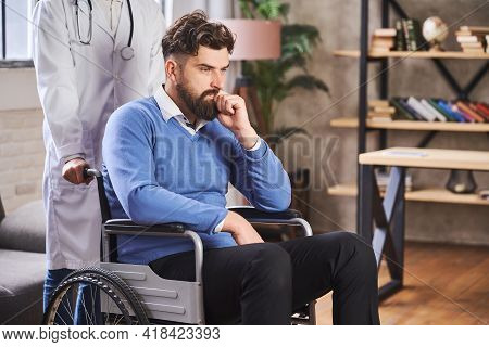 Doctor Pushing A Wheelchair Of A Thoughtful Bearded Man