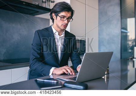 Elegant Businessman Works From Home With A Laptop. Teleworking Concept