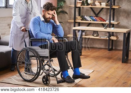 Sorrowful Disabled Man Sitting In A Wheelchair And A Doctor Pushing It