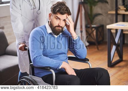 Handsome Bearded Disabled Man Sitting In A Wheelchair And A Doctor Pushing It