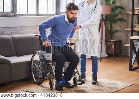 Doctor Assisting His Patient To Stand From A Wheelchair