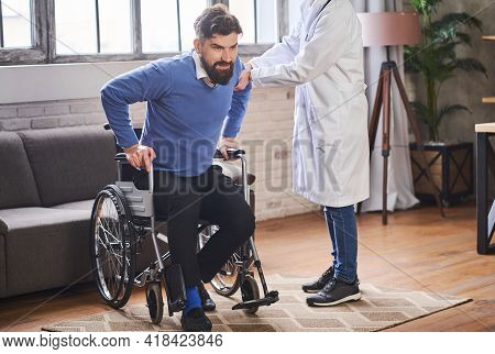 Therapist Assisting A Young Man To Stand From A Wheelchair