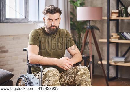 Disabled Veteran Sitting In A Wheelchair And Giving A Sad Look At The Camera