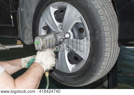 A Car Mechanic Wearing Work Gloves Uses A Pneumatic Wrench To Tighten The Nut On The Front Right Whe