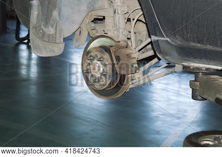 A View Of A Rusty Brake Mechanism With The Rear Right Wheel Removed On A Car That Hangs On A Lift In