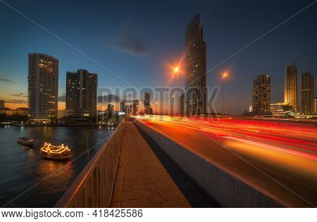 Skyscrapers And Traffic Light Trails On Taksin Bridge Crossing Chao Phraya River In Bangkok, Thailan