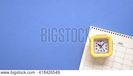 Yellow Clock On Top Of Calendar Or Planner. Planning For Meeting Or Travel Concept. Copy Space.