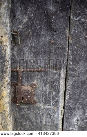 Close Up Of An Old And Deteriorated Wooden Door With A Rusty Metal Latch And A Padlock, Rural Textur