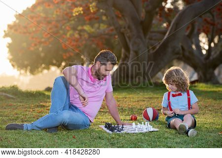 Kids Chess School. Father And Son Playing Chess Lying On Grass At Lawn Park. Fathers Day, Love Famil